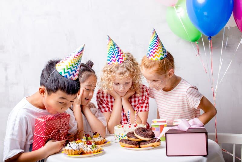 Las niñas y los muchachos impresionantes están esperando su porsion de la torta imagenes de archivo