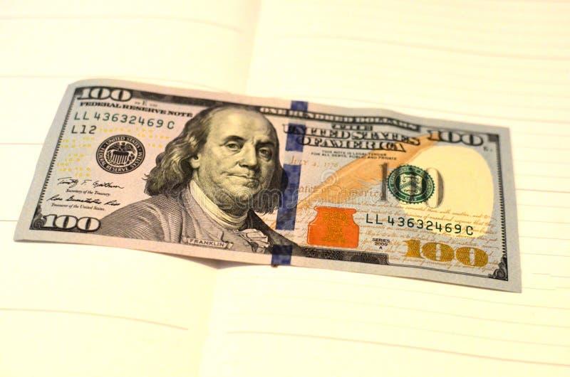 Las notas de la textura del americano ciento del dinero diseñan Pluma, lentes y gráficos Operaciones financieras imagen de archivo