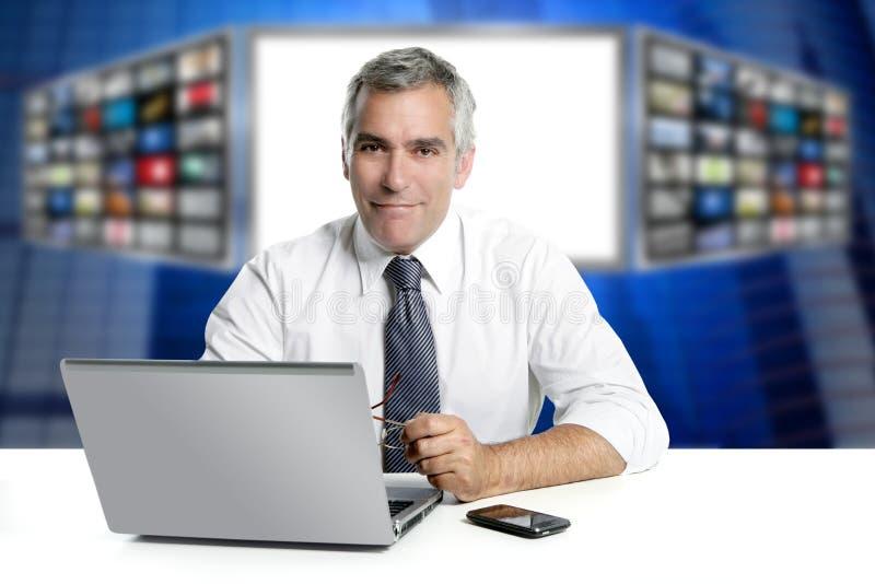 Las noticias grises del pelo TV defienden la sonrisa de la computadora portátil del presentador foto de archivo libre de regalías