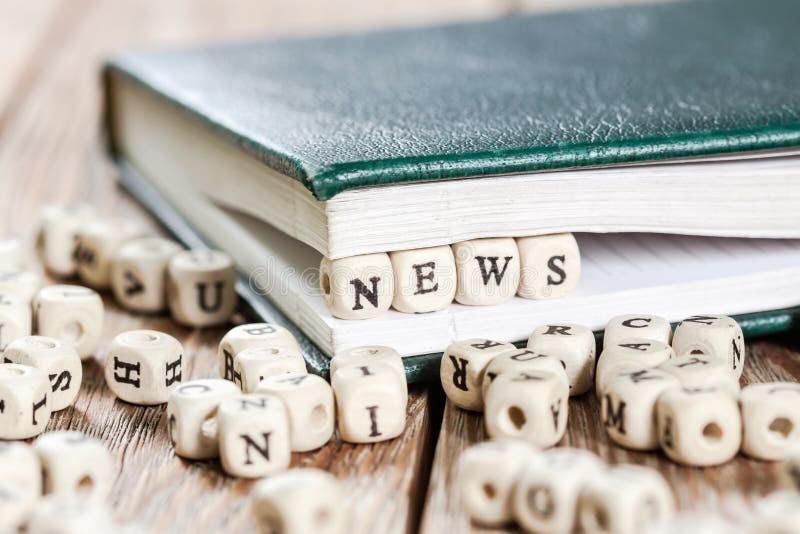 Las noticias redactan escrito en un bloque de madera imágenes de archivo libres de regalías