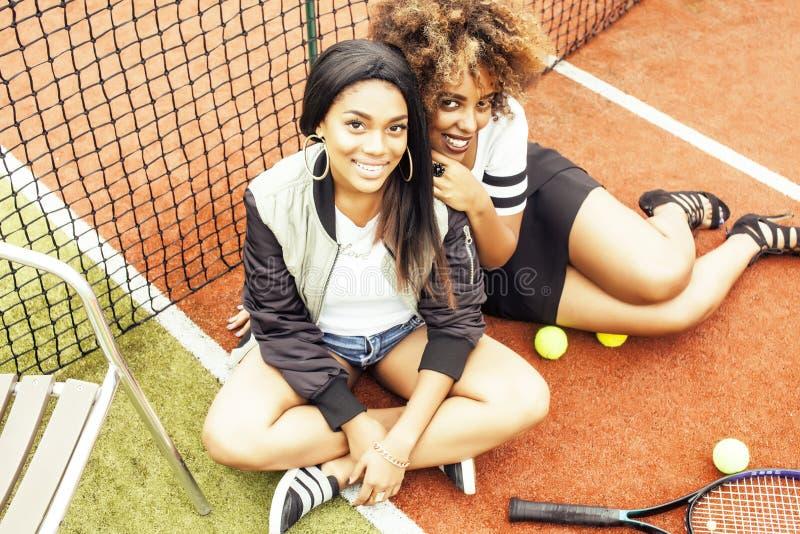Las novias bonitas jovenes que cuelgan en campo de tenis, forman el swag vestido elegante, sonrisa feliz de los mejores amigos ju fotos de archivo libres de regalías