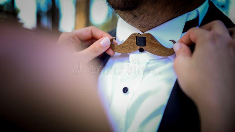 Las novias dan en el bigote formaron el bowtie de madera del cierre del novio encima de la visión foto de archivo libre de regalías