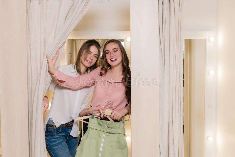Las novias felices en probador intentan encendido la ropa fotografía de archivo