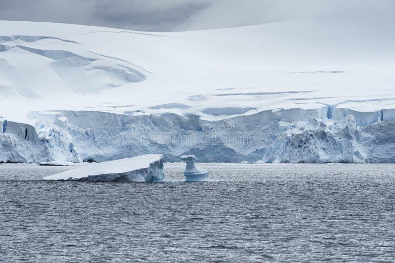 Las nubes bajas sobre la nieve capsularon las montañas y los pedazos del hielo que flotan en el Ministerio de marina aúllan foto de archivo libre de regalías