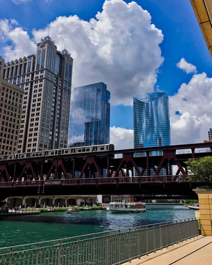 Las nubes de cúmulo forman sobre el paisaje urbano de Chicago como calle elevada icónica de Wells de las cruces del tren del ` de foto de archivo