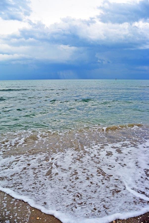 Las nubes de lluvia oscuras sobre el mar y la arena de la turquesa varan foto de archivo