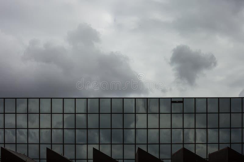 Las nubes de tormenta reflejan en ventanas del windo del espejo del edificio de oficinas imagen de archivo libre de regalías