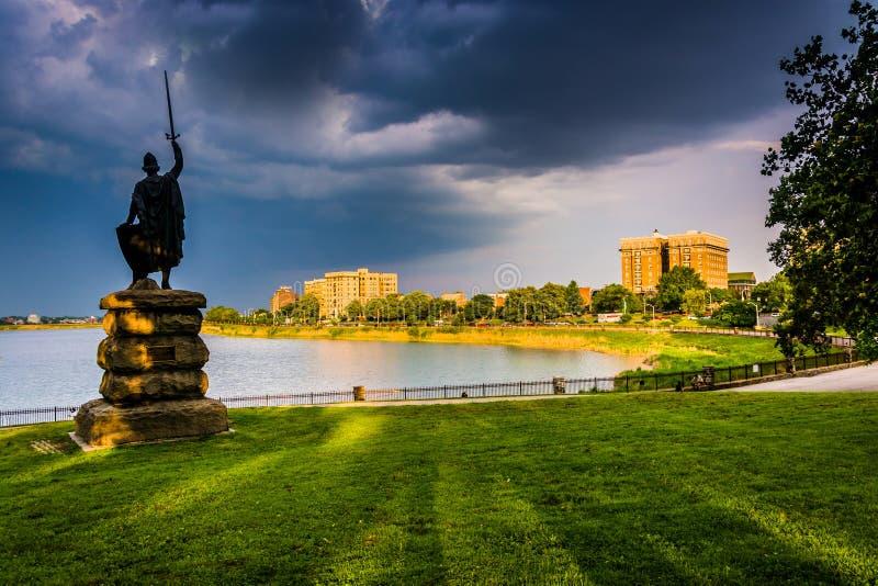 Las nubes de tormenta sobre una estatua y un lago druid en la colina del druida parquean adentro imagenes de archivo