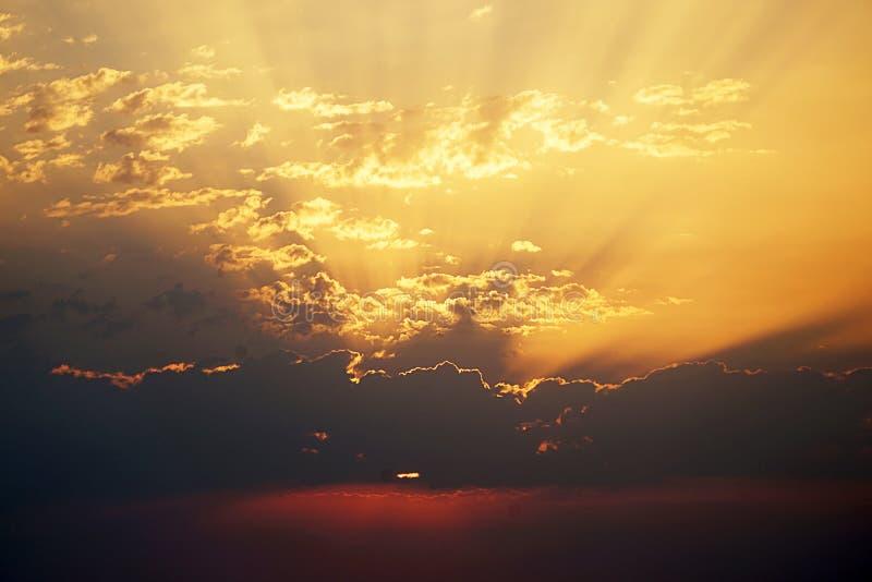 Las nubes dispersaron en un cielo rojo de la puesta del sol fotos de archivo