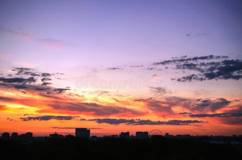 Las nubes en la puesta del sol contra el contexto de siluetas contienen un ci grande imagen de archivo