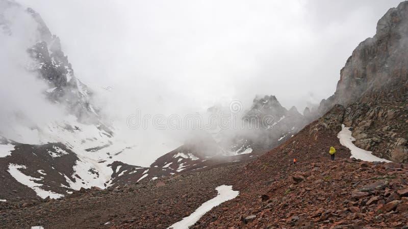 Las nubes grandes nadan a través de la garganta Un grupo de escaladores sube el pico foto de archivo