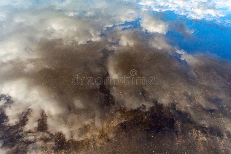 Las nubes mullidas blancas con el cielo azul que refleja en el agua de río practican surf imágenes de archivo libres de regalías