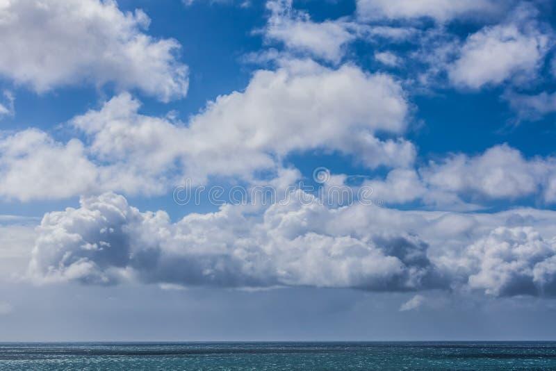Las nubes mullidas y el océano tranquilo riegan - colores azules profundos imagen de archivo