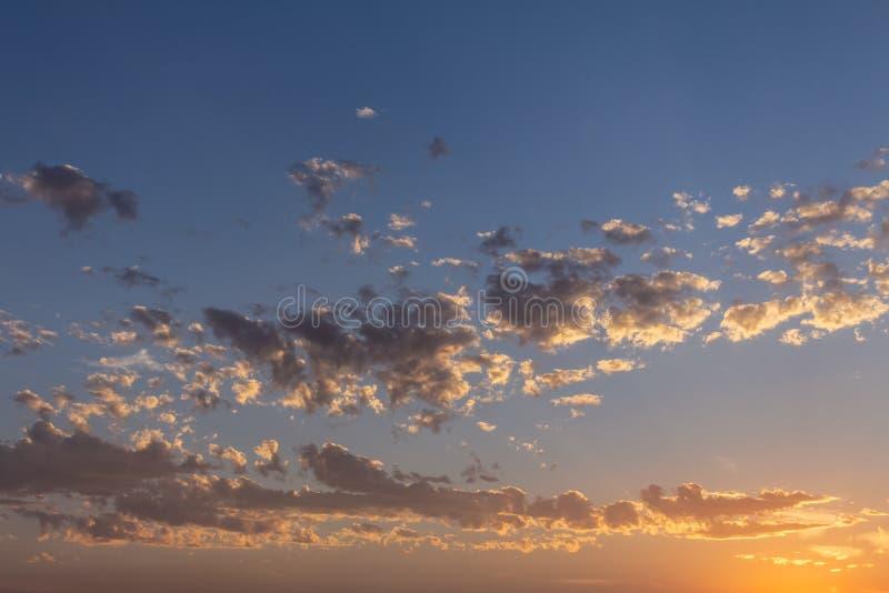 Las nubes pequeñas y numerosas se pintan en color de oro durante la puesta del sol imagen de archivo