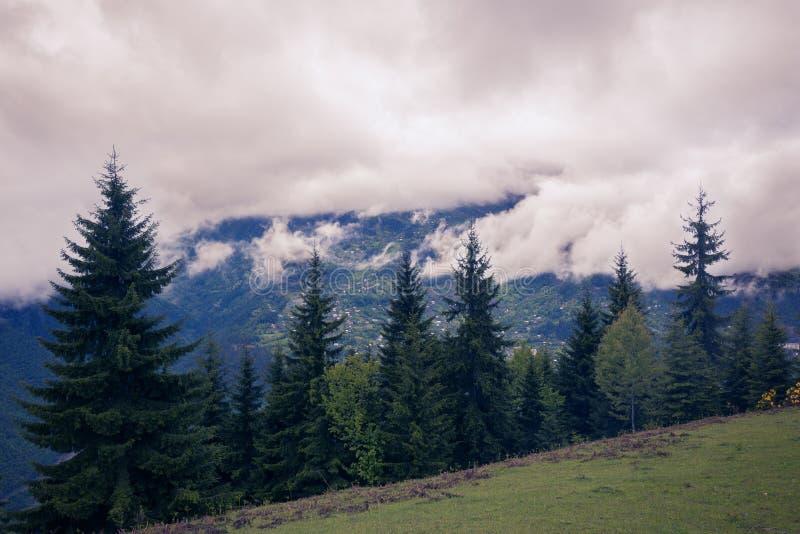 Las nubes pesadas bajas flotan sobre el valle de la montaña fotos de archivo