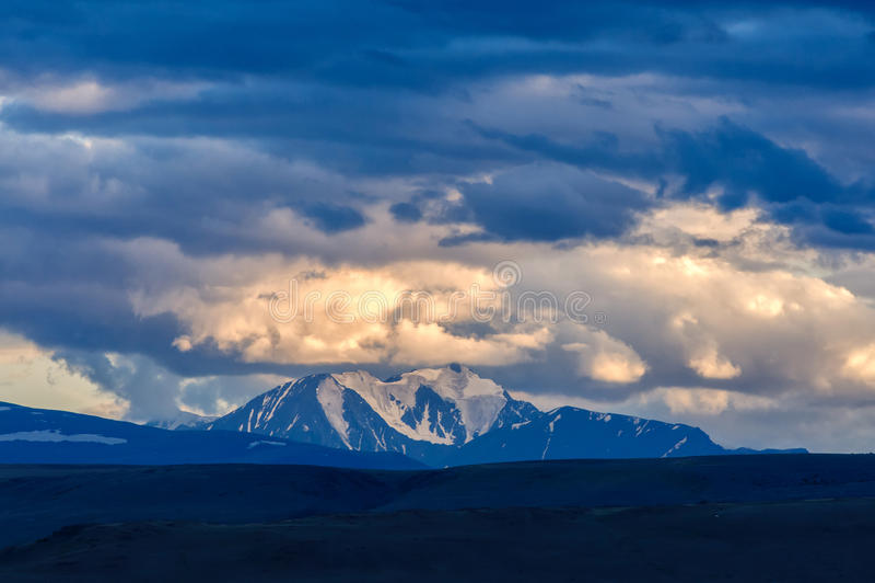 Las nubes que pasan sobre pináculo de la montaña en puesta del sol se encienden fotos de archivo libres de regalías