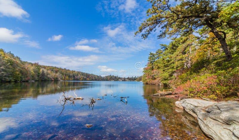 Las nubes se reflejan en un lago tranquilo Minnewaska en el Condado de Orange, NY, rodeado por el follaje de otoño brillante en u foto de archivo