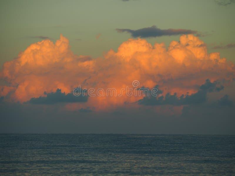 Las nubes tranquilas y majestuosas cogen los primeros rayos de un nuevo día sobre el mar fotos de archivo libres de regalías