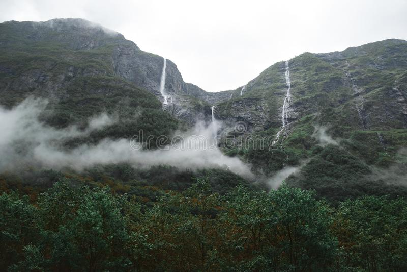 Las nubes Wispy rodean las altas cascadas de la selva tropical en Noruega foto de archivo