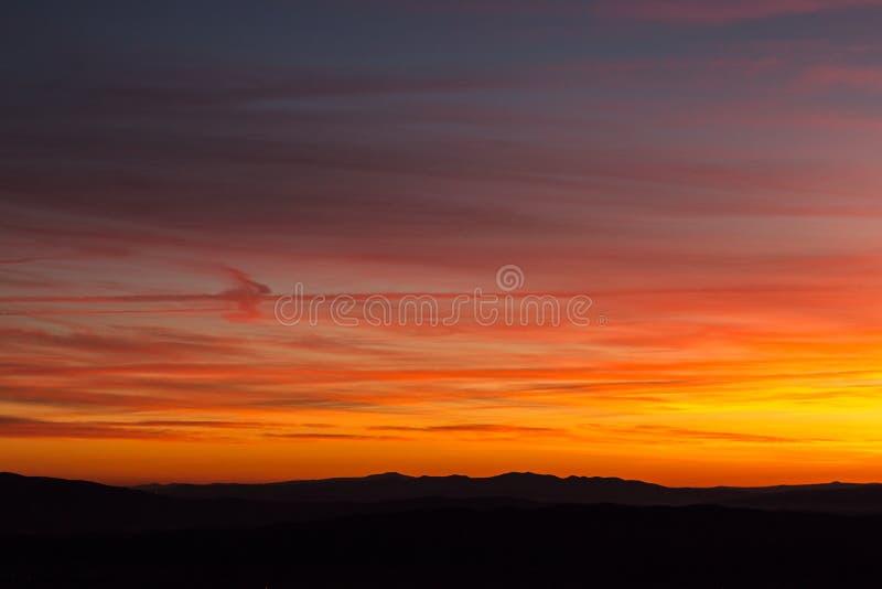 Las nubes y el vapor del jet arrastra crear textura hermosa, colorida en el cielo en la puesta del sol con perfiles de la montaña fotos de archivo libres de regalías