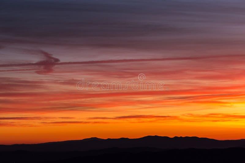 Las nubes y el vapor del jet arrastra crear textura hermosa, colorida en el cielo en la puesta del sol con perfiles de la montaña imágenes de archivo libres de regalías