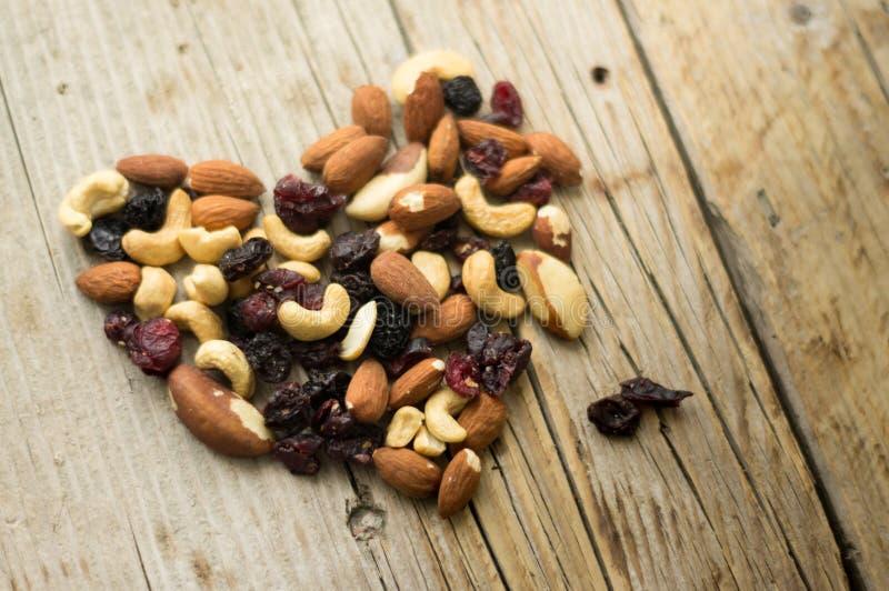 Las nueces mezcladas aisladas y las frutas secadas en el corazón forman en el fondo rústico imágenes de archivo libres de regalías