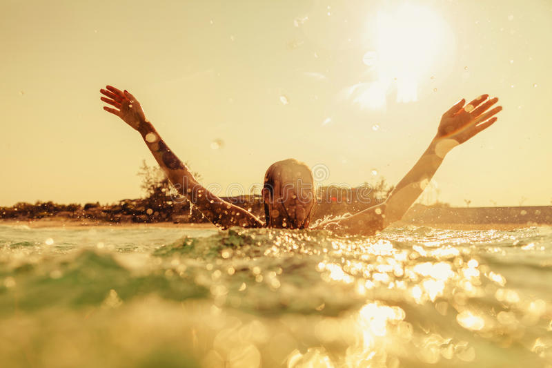 Las ondas atractivas del mar de la nadada de la muchacha del bikini salpican tono del vintage fotos de archivo libres de regalías