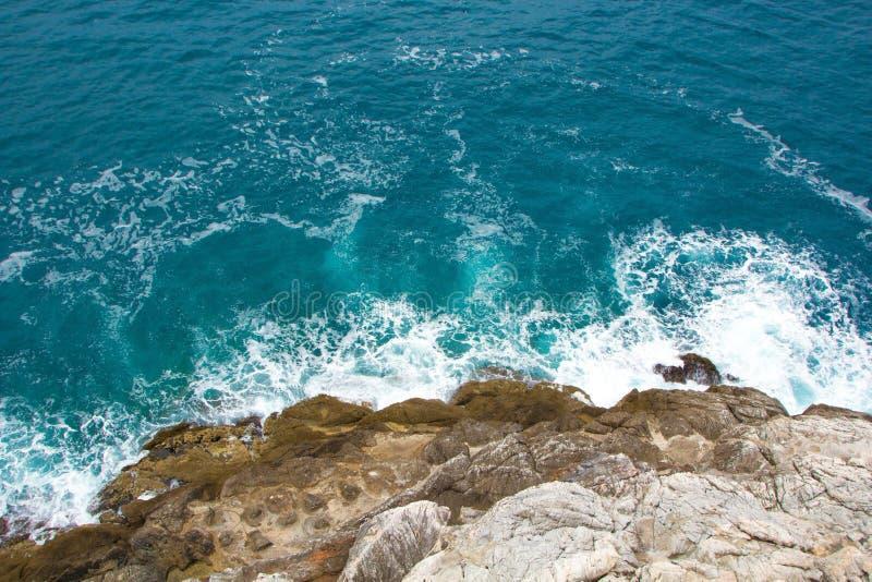 Las ondas azules azules del mar se estrellan en las rocas La espuma blanca hermosa se separa en todas las direcciones Fondo del m fotografía de archivo