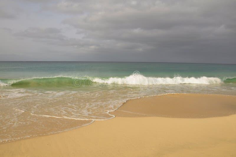 Las ondas se estrellan sobre la playa del paraíso fotos de archivo