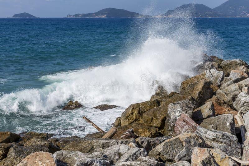 Las ondas del mar se rompen en las rocas de Tellaro, con el golfo del La Spezia en el fondo, Liguria, Italia imagen de archivo libre de regalías