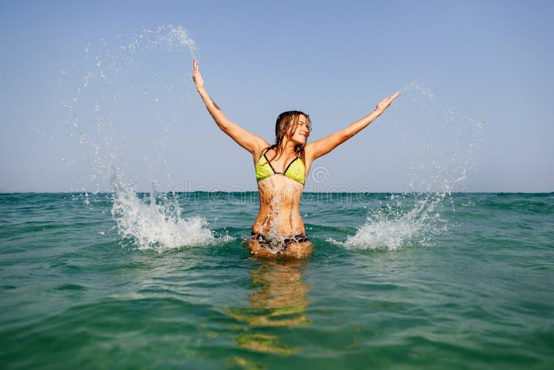Las ondas felices del mar del salto de la muchacha atractiva del bikini salpican fotos de archivo libres de regalías