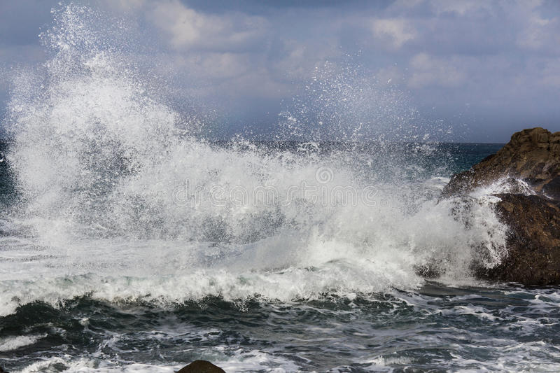 Las ondas grandes que se rompen en orilla - agite salpicar en roca imagen de archivo