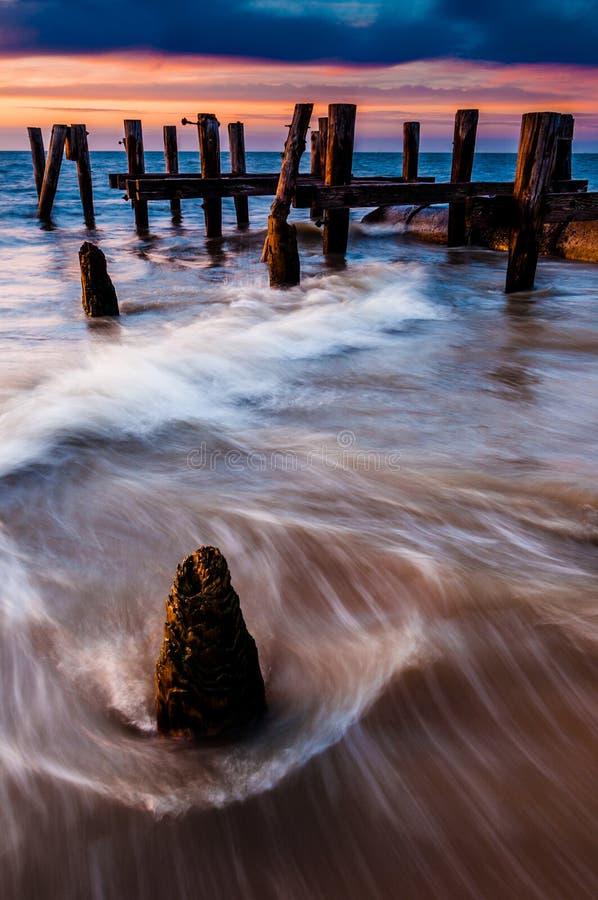 Las ondas remolinan alrededor de las virutas del embarcadero en la bahía de Delaware en la puesta del sol, s imagen de archivo