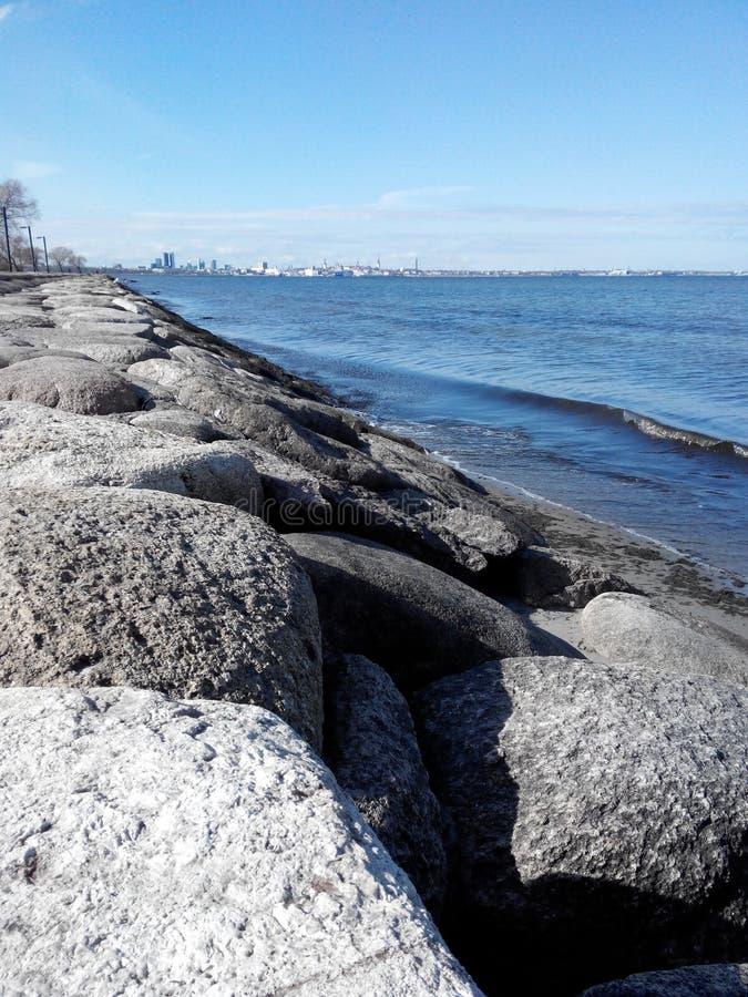 Las ondas reservadas de la resaca del mar lavan suavemente las piedras costeras de la costa de Tallinn en Estonia fotografía de archivo libre de regalías