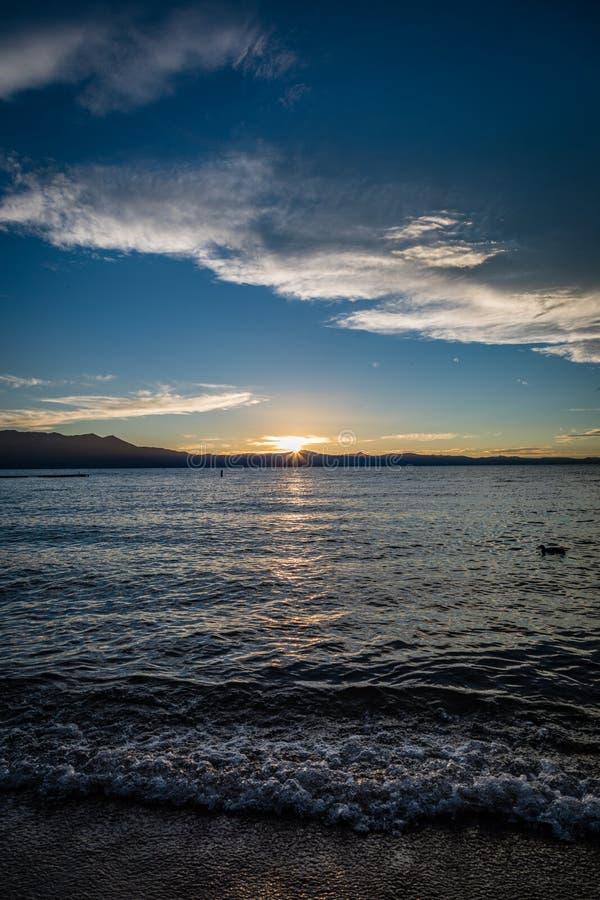 Las ondas se estrellan en la playa de la orilla del lago en el lago Tahoe durante puesta del sol con las montañas que parten el c foto de archivo