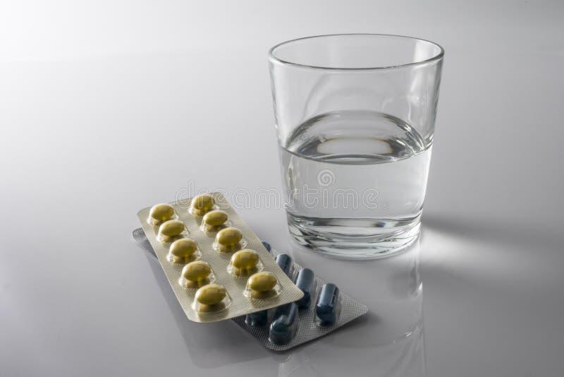 Las píldoras ampollan junto con un vidrio de agua imágenes de archivo libres de regalías