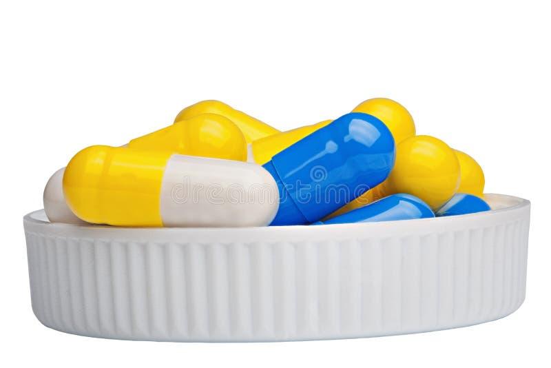 Las píldoras antibióticos están en la tapa en un fondo blanco foto de archivo libre de regalías