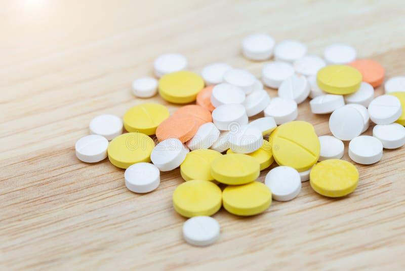 Las píldoras coloridas de la medicina hacen tabletas o drogan el primer en el fondo de madera de la tabla imagen de archivo