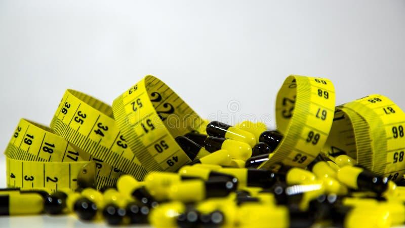 Las píldoras con la cinta métrica en el fondo blanco, representan la industria de la píldora de la dieta imagenes de archivo