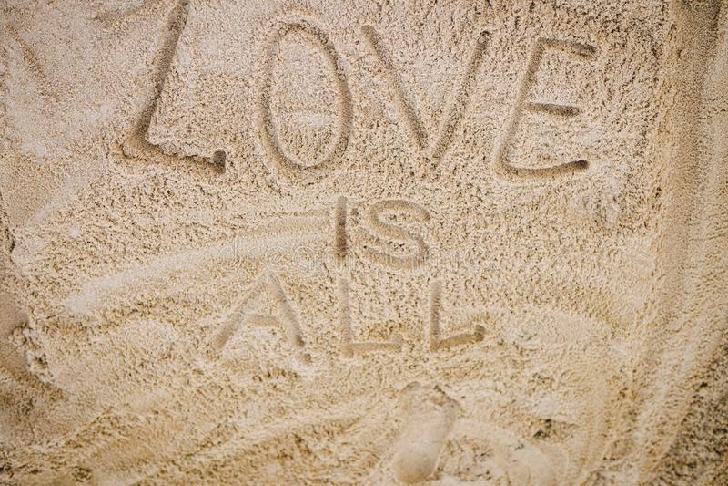 Las palabras AMAN de la escritura ESTÁN TODO en la arena de la playa imagen de archivo libre de regalías
