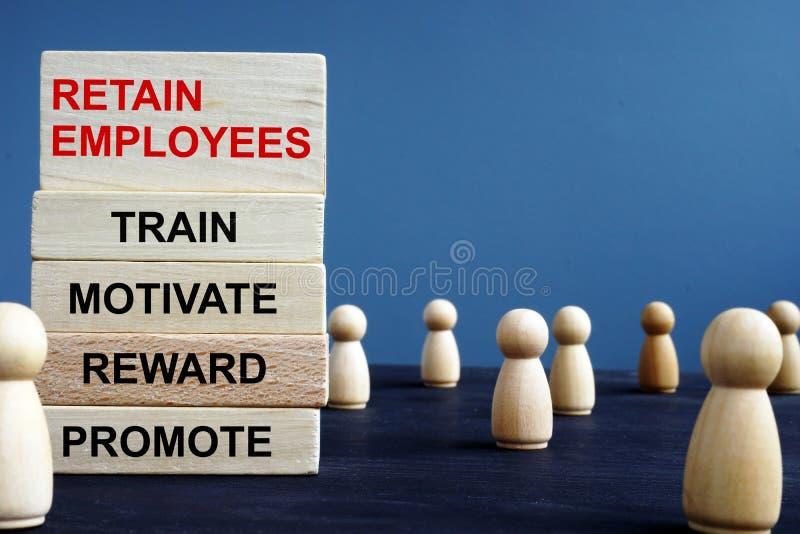 Las palabras conservan a empleados entrenan motivan la recompensa promueven en bloques de madera imagen de archivo