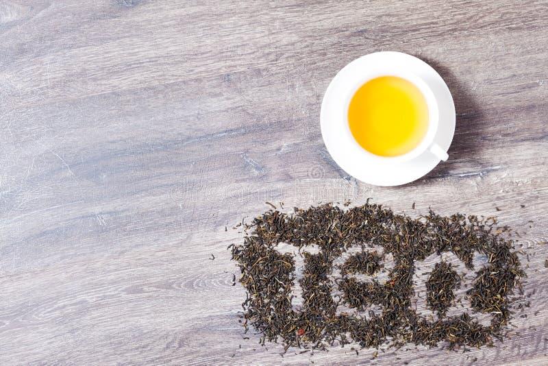 Las palabras I aman el té hecho de hojas de té verdes con una taza de té imagen de archivo