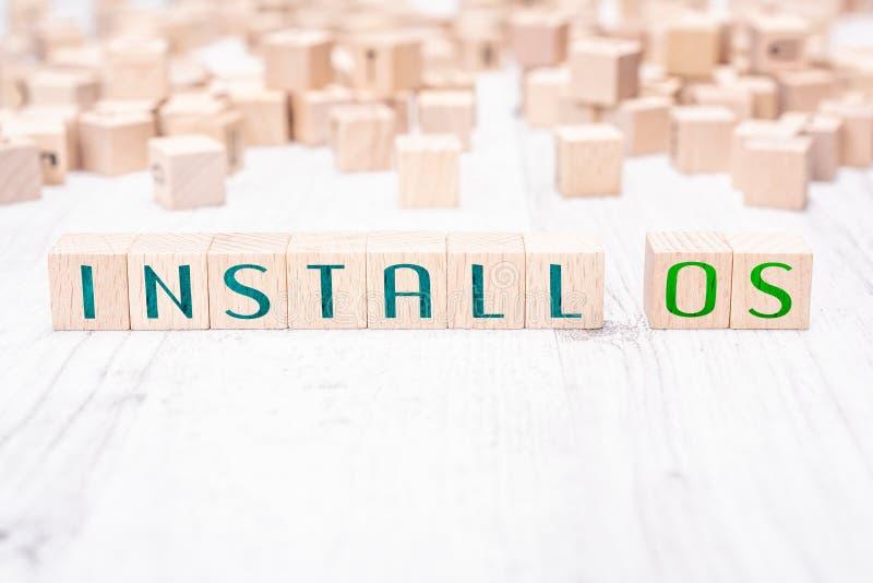 Las palabras instalan el OS formado por los bloques de madera en una tabla blanca fotos de archivo