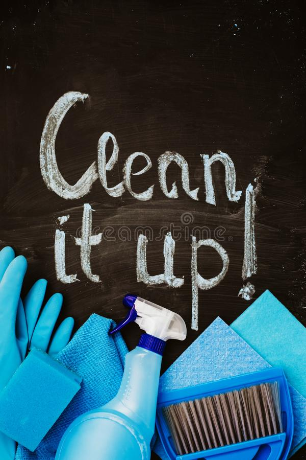?Las palabras ?lo limpian! ?escrito en tiza en una pizarra sobre las herramientas azules de la limpieza de la casa fotografía de archivo