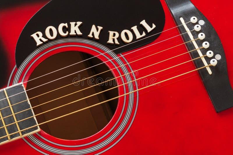 Las palabras oscilan el rollo con las letras de madera, primer de N en una superficie de la guitarra acústica roja Fondo del entr foto de archivo libre de regalías