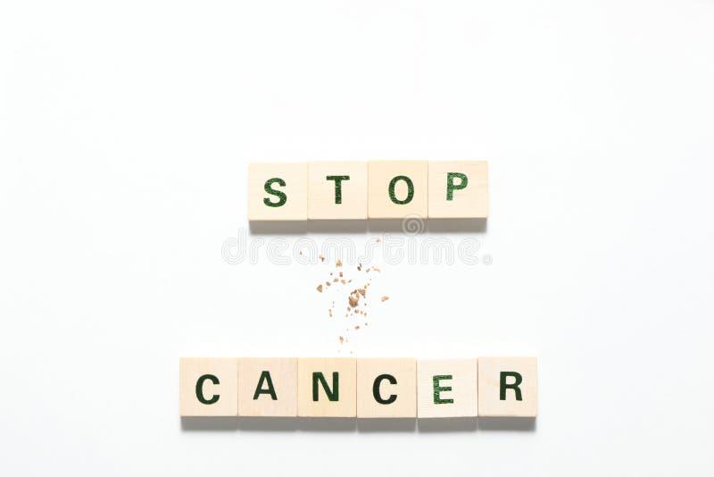 Las palabras paran el cáncer hecho de bloques de madera y algo de tabaco aislados en el fondo blanco foto de archivo