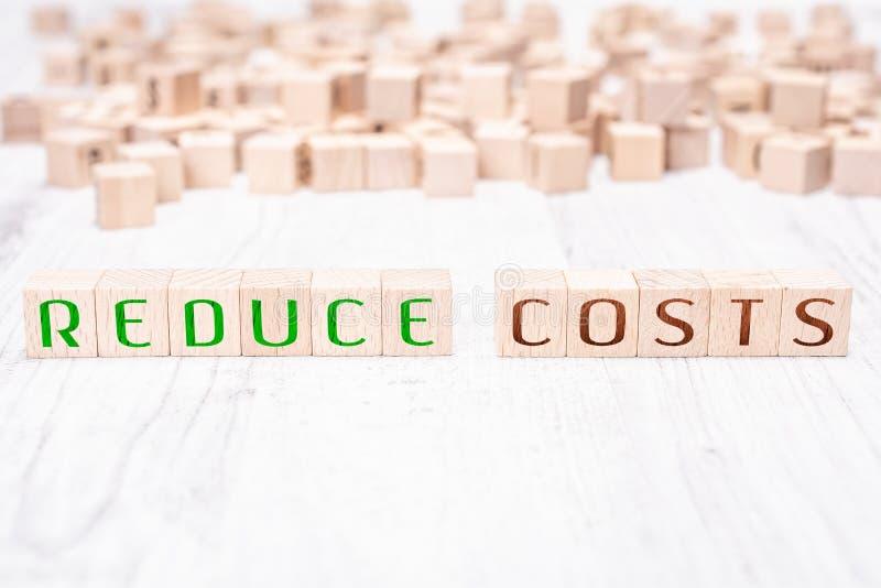 Las palabras reducen los costes formados por los bloques de madera en una tabla blanca imagen de archivo
