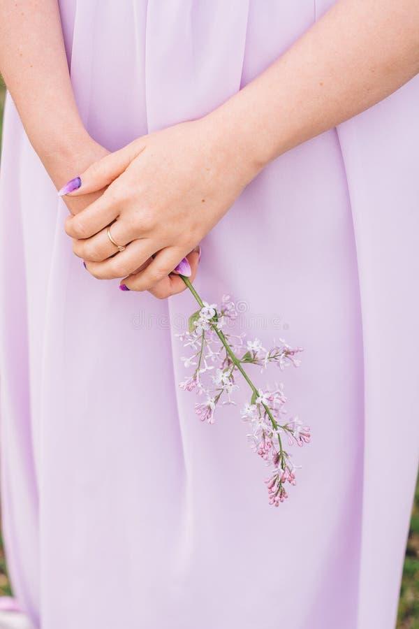 Las palmas de la muchacha en color delicado con un ramo de flores fotos de archivo
