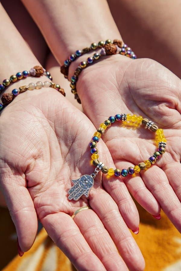 Las palmas femeninas con la gota natural empiedran las pulseras que sostienen la pulsera con el colgante fotografía de archivo libre de regalías