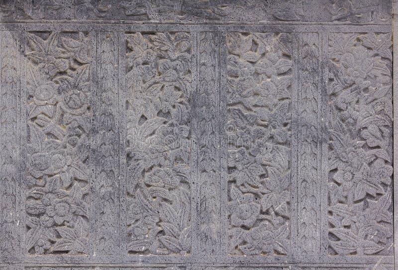 Las paredes de piedra viejas fueron talladas en las flores imagen de archivo libre de regalías